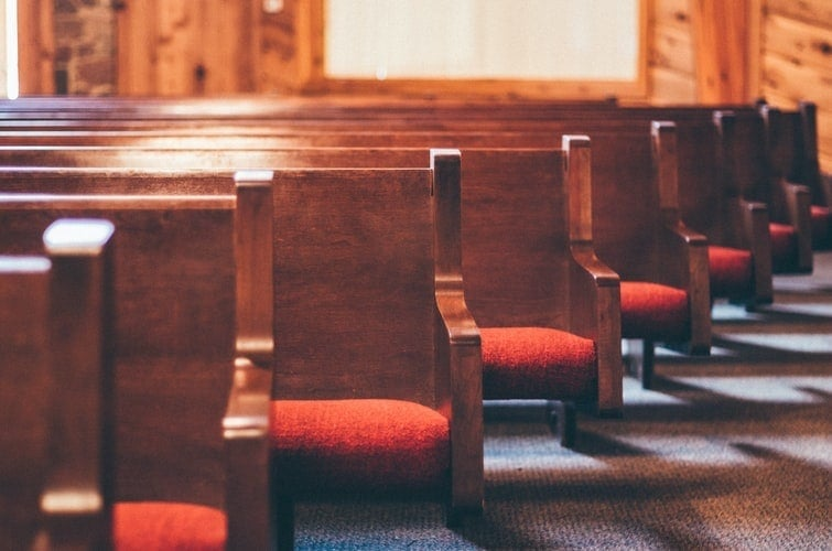 rows of pews with red cushioned seats
