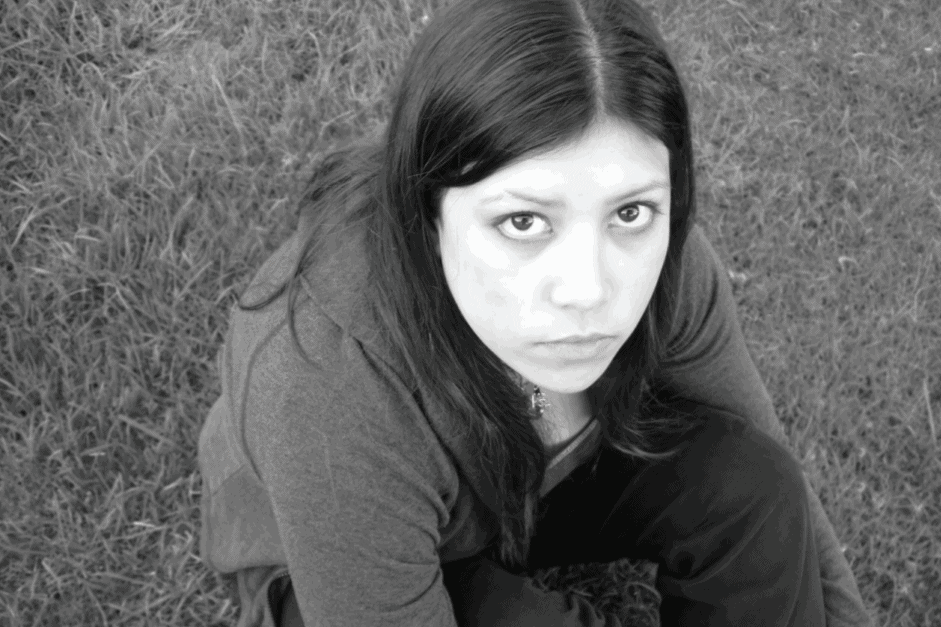 bw image of a girl sitting in the grass looking at camera