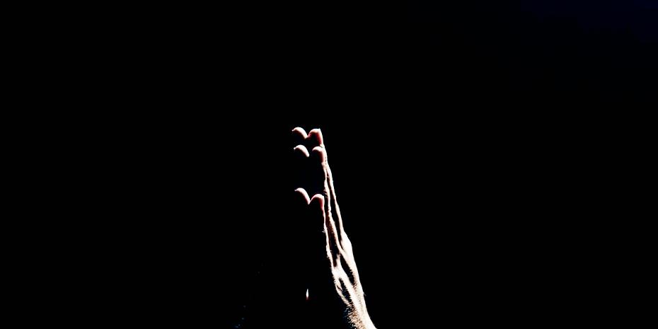 hand praying against black backdrop