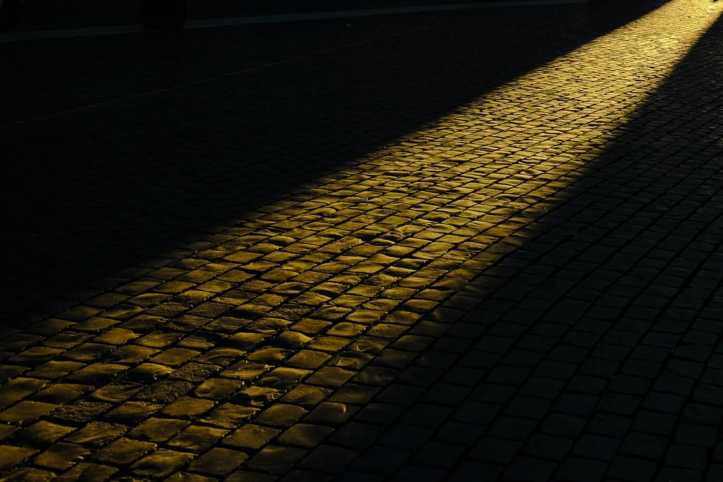 Observing light beaming on the path of cobblestone